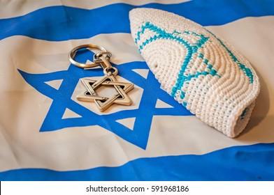 Folded Jewish customary kippah cap, a Star of David on the unfolded Flag of Israel. Judaism vs. Zionism. Israel Independence Day, Yom Hazikaron, Yom Ha'Atzmaut, Yom Hashoah, Holocaust Remembrance