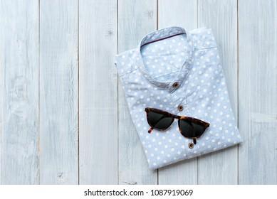 folded light blue polkadot linen shirt with sunglasses on white wooden table background.
