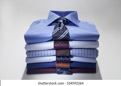 Folded Man's shirts and ties isolated on white background.