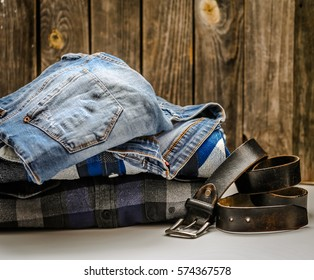 folded men's shirt in the box and the belt with jeans on wooden background ,concept of style and fashion