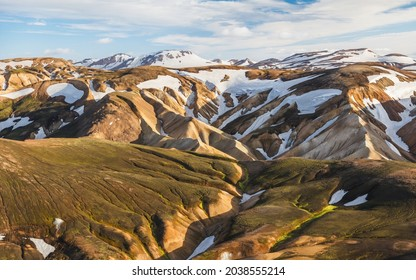 Folded mountain slopes covered with patches of snow in Landmannalaugar.