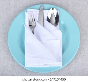 Folded napkin with fork, spoon and knife, on plate, on color background