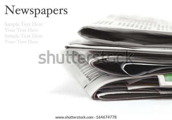 Folded newspapers on white background with copy space and easy to remove sample text. Macro image with shallow depth of focus