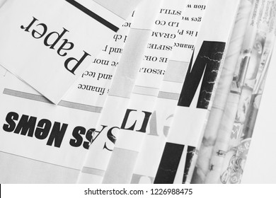 Folded newspapers with partially shown headlines and articles - blurred text and photos. Daily papers with news, business and finance journals at the office, fresh press. News template with copy space
