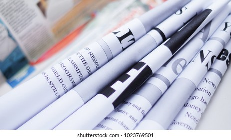 Folded newspapers with partially visible headlines against background of pages with articles - blurred text and photos. Daily papers with news, business and finance journals at the office, fresh press