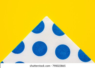 Folded paper napkin with blue polka-dots on a yellow table