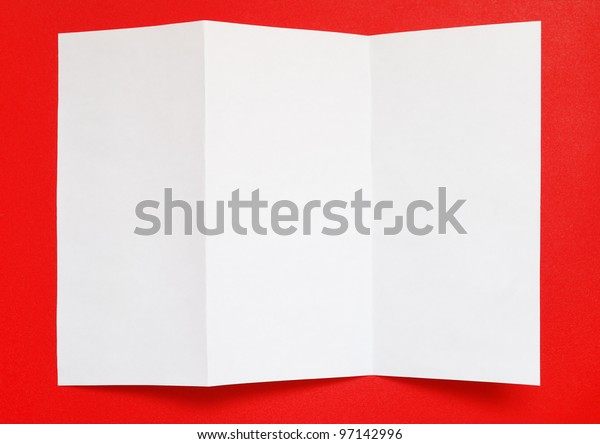 Folded paper on red background, top view