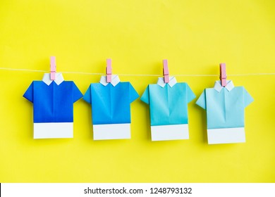Folded paper shirts hanging on clothes line