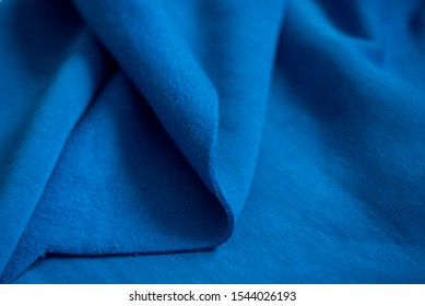 folded piece of bright blue satin fabric isolated on white background, top view. Folds of cotton fabric. warm coat. Beautiful texture of blue color. A piece of fabric for a seamstress cut