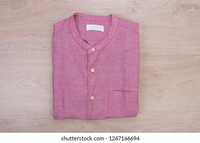 Folded pink casual shirt Mandarin collar on wooden background
