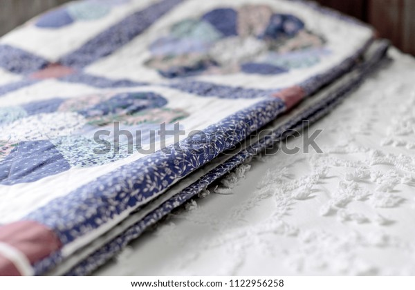 A folded quilt laying on top of a made bed and bedspread with shallow depth of field