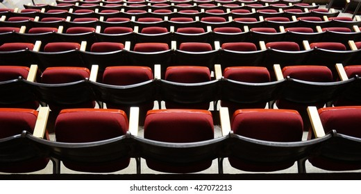 Folded red seats at a multipurpose arena and sports stadium