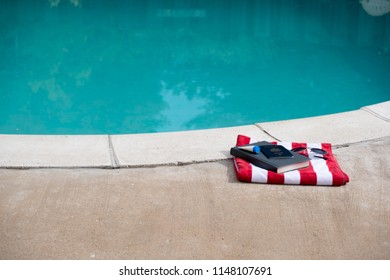 Folded red and white striped towel with hardback book, US passport, sunscreen, and aviator sunglasses by the edge of a swimming pool with calm blue water.