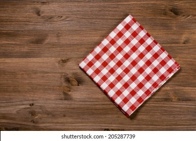 Folded red-white napkin on wooden table