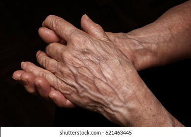 Folded senior woman wrinkled hands close up. On abstract background, clipping path included. Old age, age problems, poverty and loneliness theme