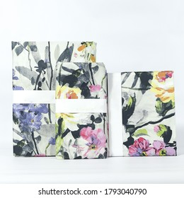 A folded set of decorative floral bedlinens on a white background