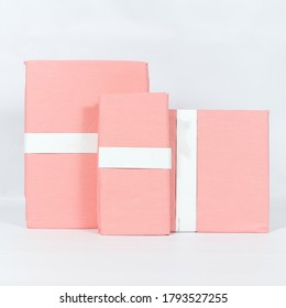 A folded set of decorative pink bedlinens on a white background