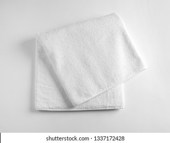 Folded soft terry towel on light background, top view