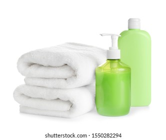 Folded soft towels and toiletries on white background