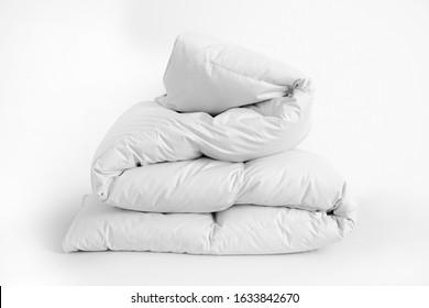 Folded soft white duvet, blanket or bedspread, against white background. Close up photo
