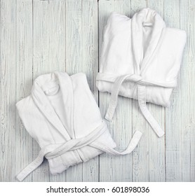 Folded spa bathrobes on wooden background