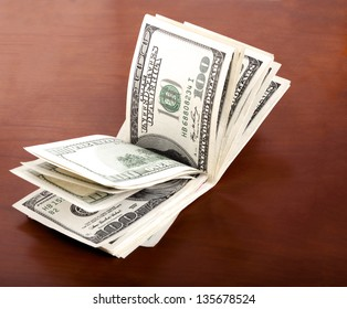 A folded stack of 100 US$ money notes on brown wooden background.