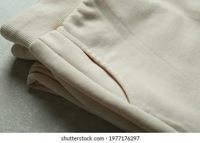 Folded sweatpants on white textured background, close up