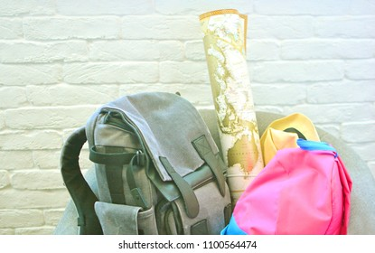 Folded things for travelling. Two backpacks with things to go, map and hat in a grey home chair.