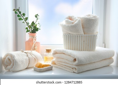 Folded towels stack,essential oil and soap on window sill empty copy space.Body care concept,hotel backdrop,bathroom items.