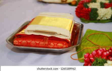 Folded traditional Kerala kasavu saree and red silk saree on a dish during Indian wedding