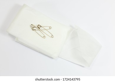 Folded triangular bandage with safety pins on top