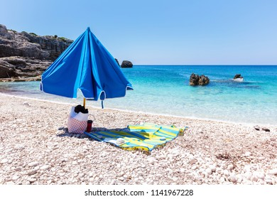 Folded umbrella with bag and bedding on the beach