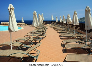 Folded umbrellas and pool chairs on the sun terrace in the hotel recreation area.