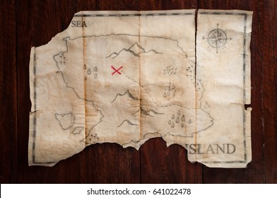 Folded vintage treasure map with red cross of Pirate chest on wood table background
