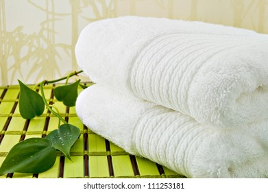 Folded white bath towels and ivy plant./White Bath Towels