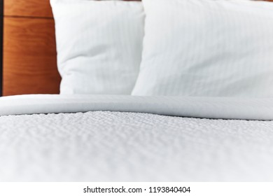 Folded white bed covers and pillows on a made bed with shallow depth of field