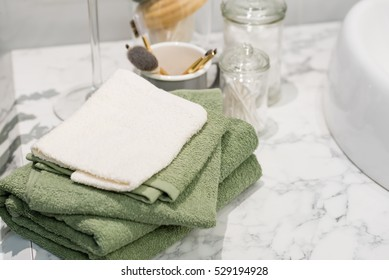 folded white and green cotton towel on a marble bathroom counter