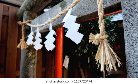 Folded white papers (Shide) hang on a Shinto sacred rope (Shimenawa) tied around a traditional Japanese gate (Torii gate) at the entrance to a shrine