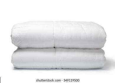 Folded white quilt on white background