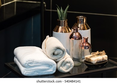 folded white towel with ceramic vases on black glass table
