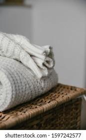 folded white wool sweater on the wicker basket