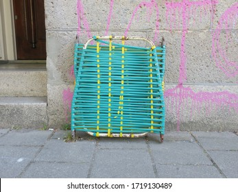 a folded worn out strechter leaning against a wall on the sidewalk