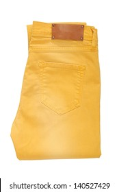 Folded yellow jeans are on white background.