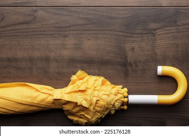 folded yellow umbrella on the brown background
