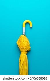 folded yellow umbrella on turquoise blue background. flat lay image of yellow umbrella vertical orientation