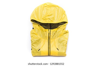 Folded yellow zipper windbreaker jacket, rain proof jacket hoodie. Track jacket sport shiny nylon full zip isolated on white. Folded clothes.
