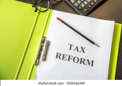 Folder and documents about Tax Reform with calculator and glasses on table background.