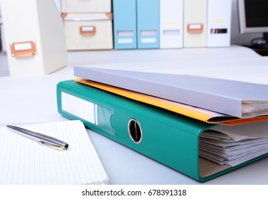 Folder file, note and pen on the desk. blurred background.