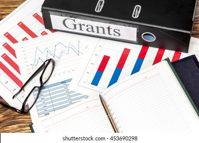 """Folder labeled """"Grants"""", glasses and notepad on graphs"""