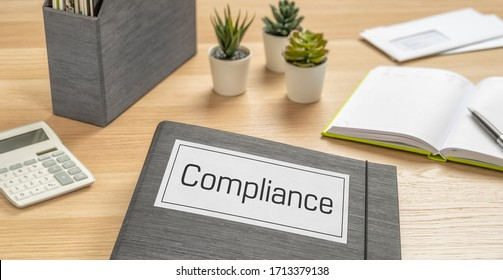 A folder on a desk with the label Compliance